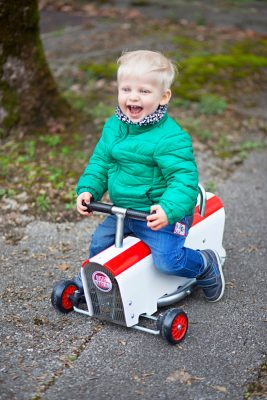 Petit garçon sur porteur en bois blanc et bandes rouges.