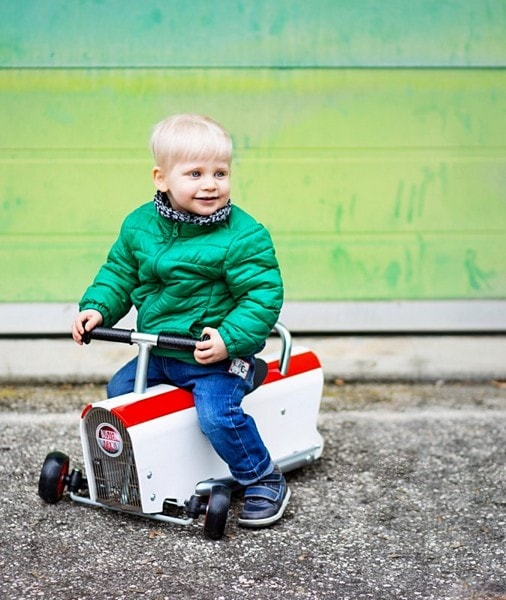 Jeune garçon blond sur le porteur en bois blanc et rouge devant porte de garage verte
